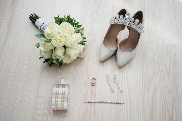 Primo piano di fedi nuziali e altri accessori durante la riunione della sposa. nozze.