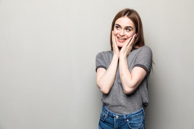 Primo piano di felice stupito giovane donna sembra sorpreso con la bocca spalancata, tocca le guance, si erge su muro beige.
