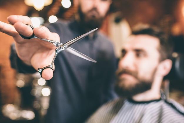 Primo piano di forbici che il parrucchiere sta tenendo. le forbici sono aperte. il cliente è pronto per la procedura.