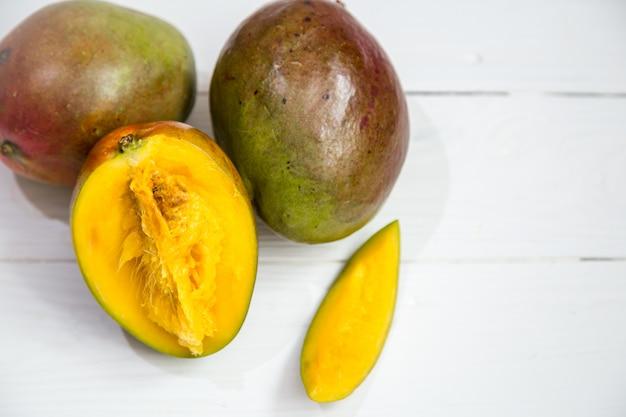 Primo piano di frutti di mango su fondo di legno bianco,
