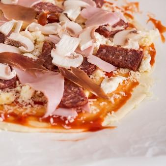 Primo piano di funghi; prosciutto; salame e formaggio su pane di pizza crudo sopra la carta pergamena