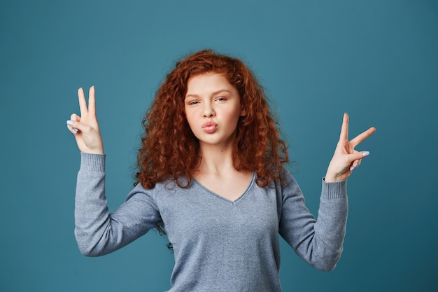Primo piano di gioiosa giovane donna con i capelli rossi ondulati e le lentiggini con gesto di pace su entrambe le mani, rendendo le labbra di anatra in posa per la foto sulla festa.