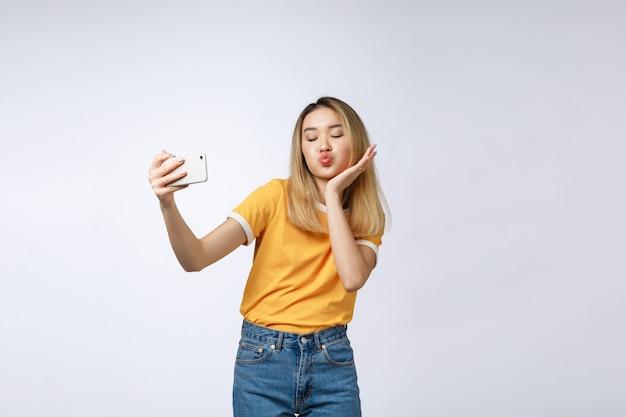 Primo piano di giovane bella donna asiatica che prende selfie
