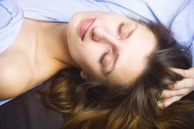 Primo piano di giovane bella donna nella menzogne blu a letto. bellezza naturale. . stile cinematografico