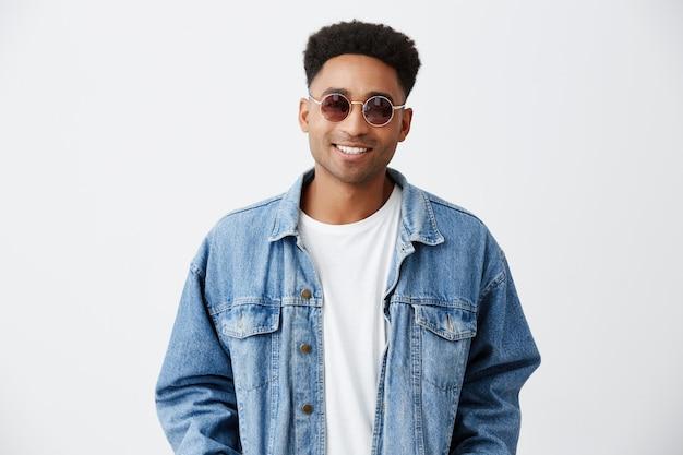 Primo piano di giovane bello allegro alla moda uomo dalla pelle scura con acconciatura afro in camicia bianca sotto giacca di jeans e occhiali da sole sorridente con i denti, guardando a porte chiuse con felice expressio