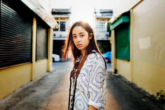 Primo piano di giovane donna asiatica in piedi sul lato della strada