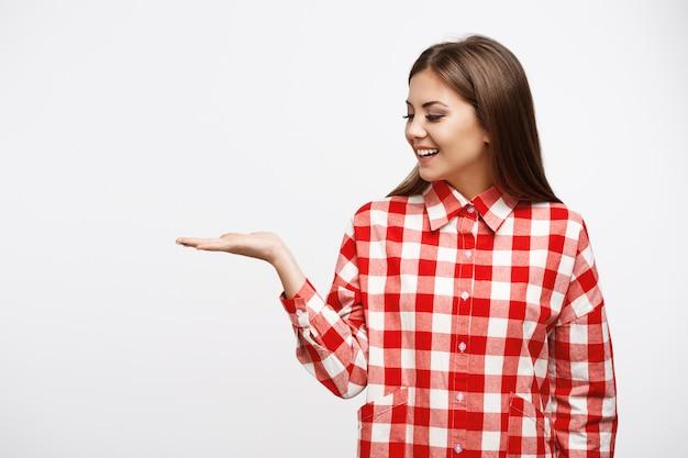 Primo piano di giovane donna attraente in camicia con la mano in su