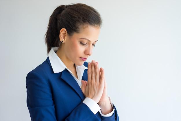 Primo piano di giovane donna caucasica calma che mette insieme le mani nella preghiera.