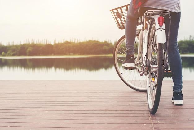 Primo piano di giovane donna pantaloni a vita bassa tenendo il piede sul peda bicicletta