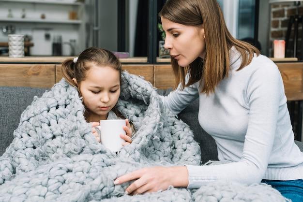 Primo piano di giovane madre prendersi cura di sua figlia malata tenendo la tazza in mano