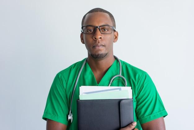 Primo piano di giovane medico afroamericano serio con la cartella.