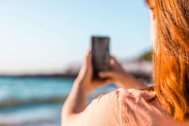 Primo piano di giovane ragazza in una maglietta estiva indietro fa una foto del mare o dell'oceano sulla riva
