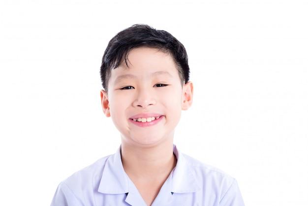 Primo piano di giovane scolaro asiatico che sorride sopra la priorità bassa bianca