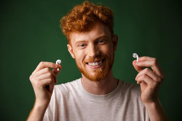 Primo piano di giovane sorridente sorridente riccio barbuto giovane in maglietta bianca, mostrando airpods