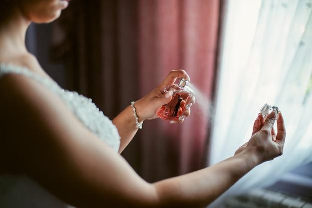 Primo piano di giovane sposa si prepara con profumi a casa al mattino il giorno del matrimonio