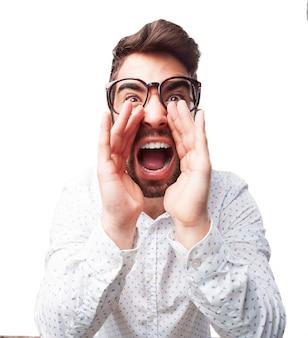 Primo piano di giovane uomo con gli occhiali che urla