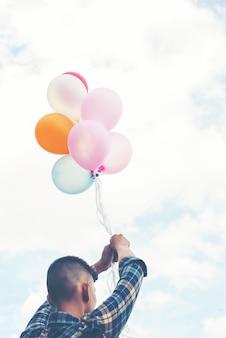 Primo piano di giovane uomo con palloncini in mano