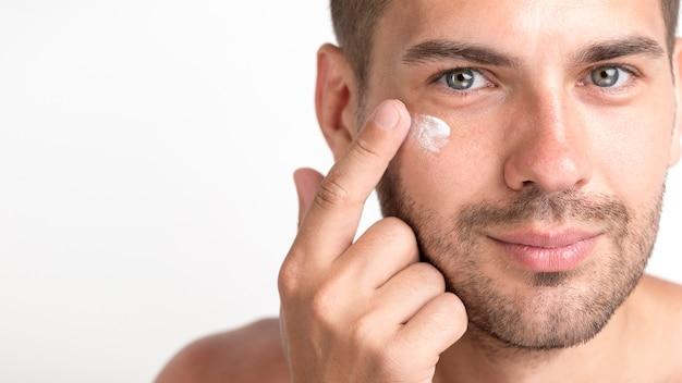 Primo piano di giovane uomo di stoppie che applica crema sul suo fronte
