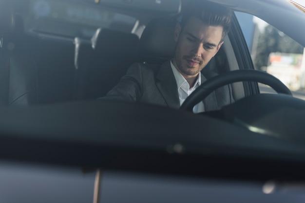 Primo piano di giovane uomo seduto in macchina
