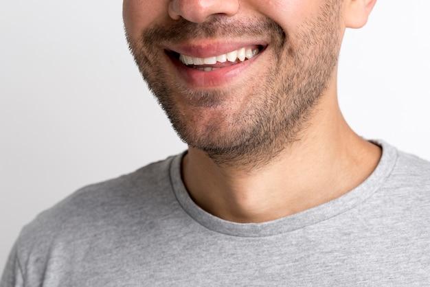 Primo piano di giovane uomo sorridente in maglietta grigia su sfondo bianco