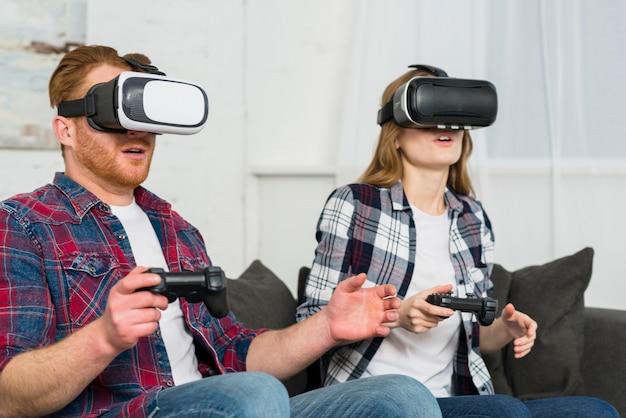 Primo piano di giovani coppie che si siedono sul sofà facendo uso di una cuffia avricolare di realtà virtuale mentre giocando video gioco