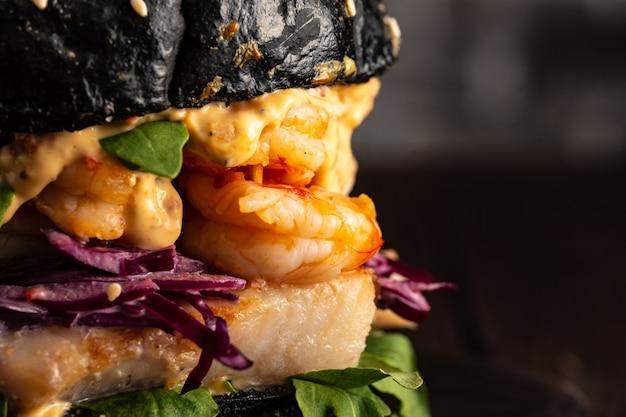 Primo piano di hamburger nero con pesce e gamberetti, fishburger con gamberi