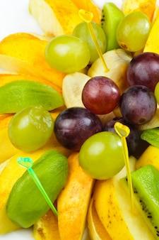 Primo piano di insalata di frutta a fette su stuzzicadenti
