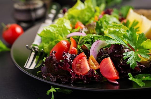Primo piano di insalata di verdure su fondo scuro.