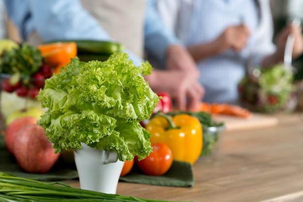 Primo piano di lattuga fresca verde in contenitore bianco sul contatore di legno