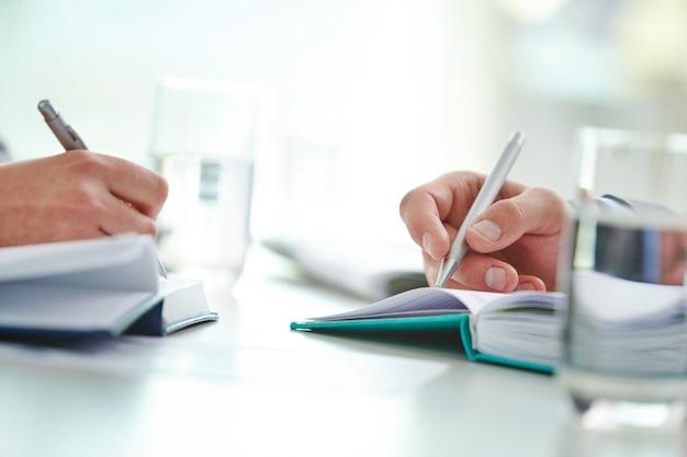 Primo piano di lavoratori scrittura con penna