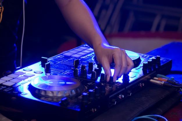Primo piano di mani dj sul palco di miscelazione, disc jockey e mixare tracce su controller mixer audio, riproduzione di musica al bar, discoteca tech o night club party.