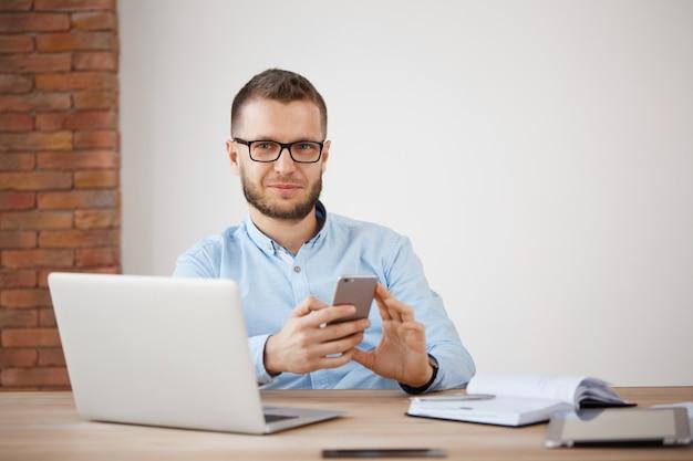 Primo piano di maturo maschio con la barba lunga manager in bicchieri e camicia seduto in ufficio, lavorando su un computer portatile