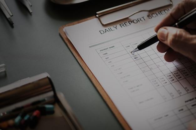 Primo piano di medico che controlla la lista di controllo quotidiana paziente del rapporto
