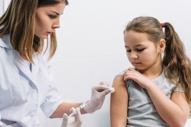 Primo piano di medico femminile che inietta la siringa sul braccio del paziente contro fondo bianco