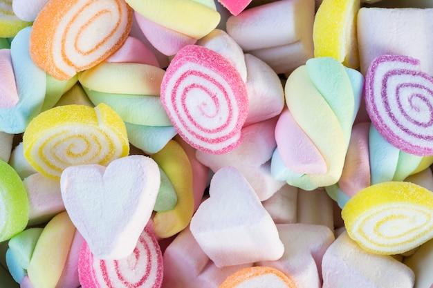 Primo piano di mini marshmallows colorati con sfondo di caramelle o texture.