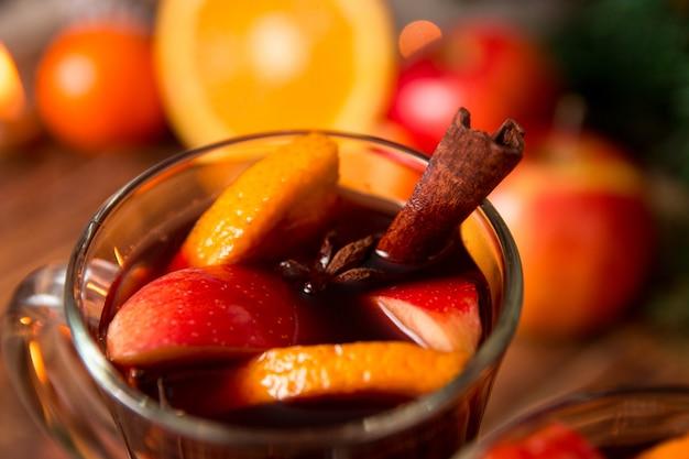 Primo piano di natale vin brulè con frutta, candele e spezie.