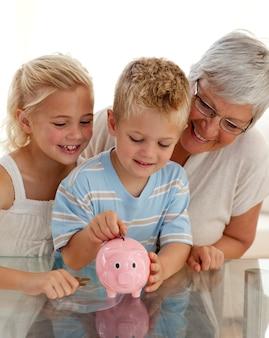 Primo piano di nonna e bambini risparmiando denaro