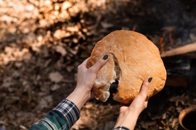 Primo piano di pane rustico fresco in mano di una donna.