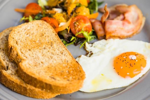 Primo piano di pane tostato; uova fritte; insalata e pancetta sul piatto in ceramica grigia