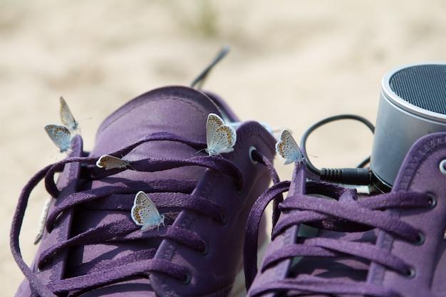 Primo piano di parecchie belle farfalle che si siedono sulle scarpe da tennis viola nella spiaggia
