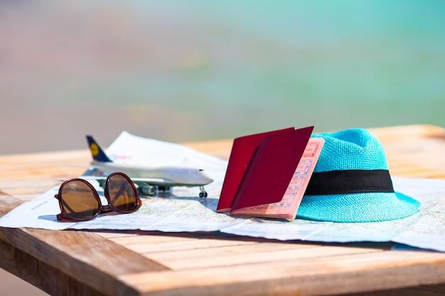 Primo piano di passaporti, aeroplanino giocattolo, occhiali da sole sulla mappa
