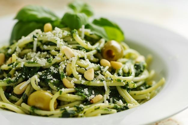 Primo piano di pasta bella saporita con spinaci, formaggio, olive, basilico e noci.