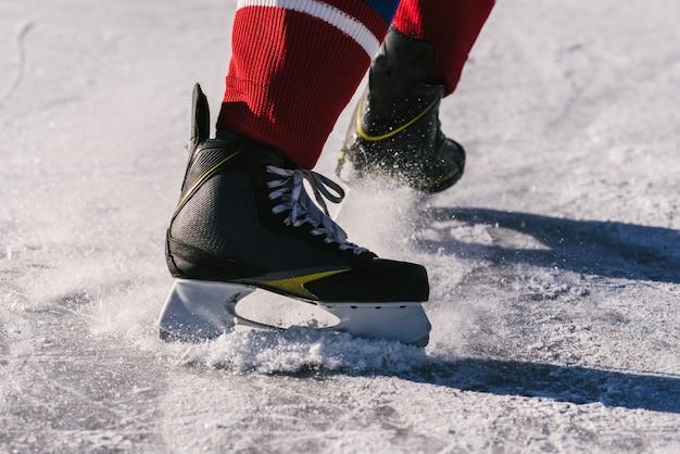 Primo piano di pattini da hockey durante una partita sul ghiaccio