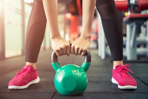 Primo piano di persone che si esercitano con kettlebell in palestra allenamento sportivo e fitness