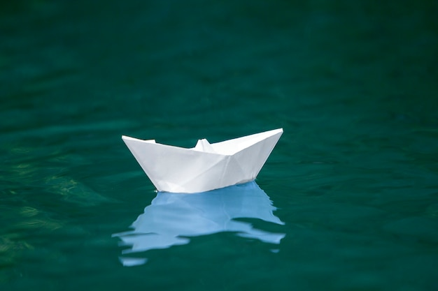 Primo piano di piccola barca bianca semplice della carta di origami che galleggia tranquillamente in chiaro fiume blu o acqua di mare sotto il cielo luminoso di estate. concetto di libertà, sogni e fantasie, scena copyspace.