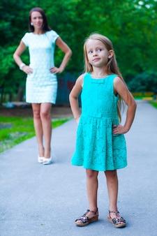 Primo piano di piccola ragazza di moda su sfondo di giovane madre