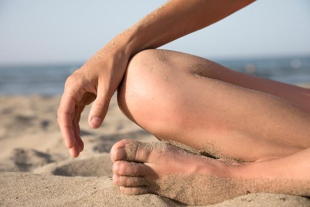 Primo piano di piedi coperti di sabbia in spiaggia