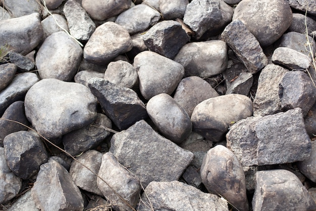Primo piano di pietra grigia. trama di pietra. ciottoli grigi sparsi. sfondo percorso di pietra sopra. ghiaia.