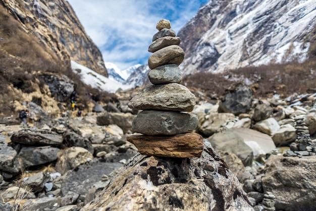 Primo piano di pietre una sopra l'altra circondate da rocce coperte di neve sotto la luce del sole