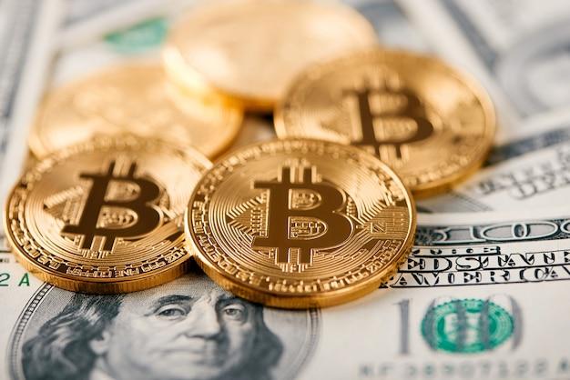 Primo piano di più grande criptovaluta mondiale di bitcoin che si trova su una priorità bassa di cento banconote del dollaro.